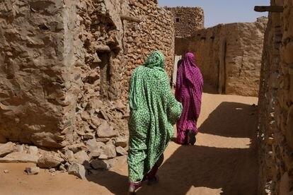 Mujeres caminando por la ciudad antigua de Chinguetti, que conserva el trazado urbano característico de las ciudades caravaneras y la técnica constructiva tradicional de casas de piedra.