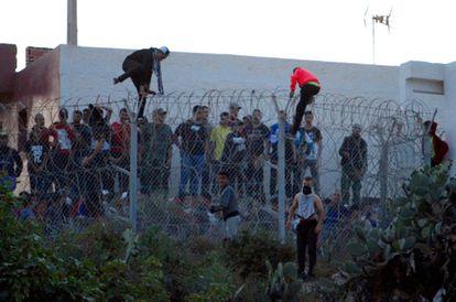 Un grupo de jóvenes marroquíes saltan la valla marroquí que separa Marruecos de la valla española en Melilla, este viernes.