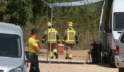 Dos bomberos trasladan una bombona de butano.