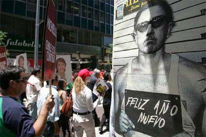 Partidarios de Bachelet pasan junto a un cartel con una imagen de Pinochet, en Santiago.