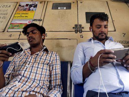 Dos viajeros usan sus teléfonos móviles en el metro de Bombay, India.