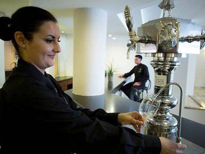 La dueña de un restaurante sirve agua de grifo refrigerada a un cliente.