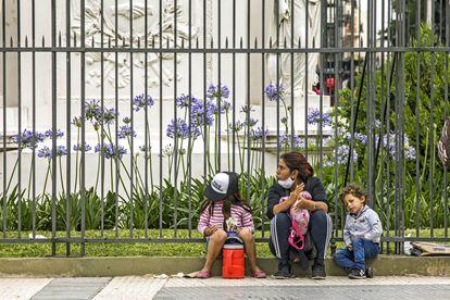 Una mujer con sus dos hijos pide ayuda en una calle de Buenos Aires, el 4 de diciembre.