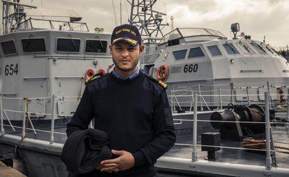 El comandante Nasser Al Gamudi posa frente a dos barcos donados por Italia a los guardacostas libios en el puerto de Trípoli, Libia.