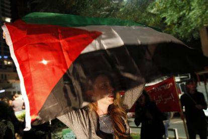 """Una mujer israelí se manifiesta en Tel Aviv a favor de la resolución de la ONU de admitir como """"Estado observador"""" a Palestina."""