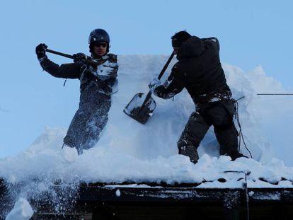 Miembros del ejército austríaco quitan nieve de un tejado en Werfenweng.