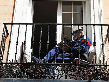 Un hombre lee en un balcón, el Primero de Mayo en Madrid.