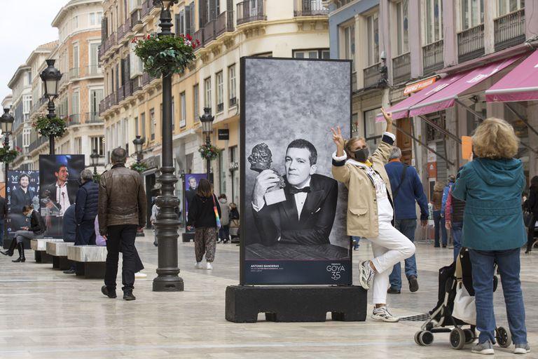 Una mujer se fotografía junto a una imagen de Antonio Banderas en calle Larios, en Málaga.