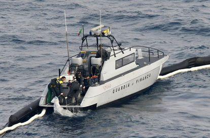 Una patrulla de policía sube a bordo un cadáver recuperado del crucero.