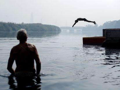 Un niño salta al río Yamuna mientras un hombre observa durante una mañana con niebla en el casco antiguo de Nueva Delhi, en octubre de 2020.