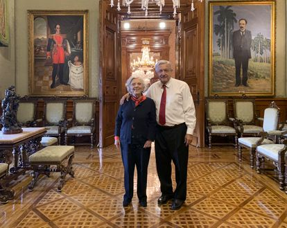 López Obrador and the writer Elena Poniatowska pose for a photograph with a painting of Simón Bolívar on their back.