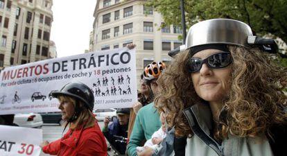 Una ciclista, con un cazo en la cabeza, ridiculiza el uso del casco.