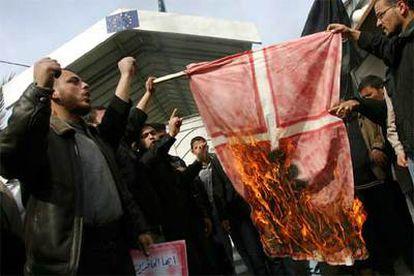 Militantes del grupo palestino Comité de Resistencia Popular queman una bandera de Dinamarca en Gaza.