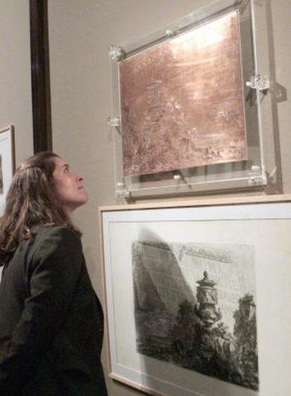 Una mujer contempla la plancha de cobre de Piranesi que se exhibe en la pìnacoteca bilbaína.