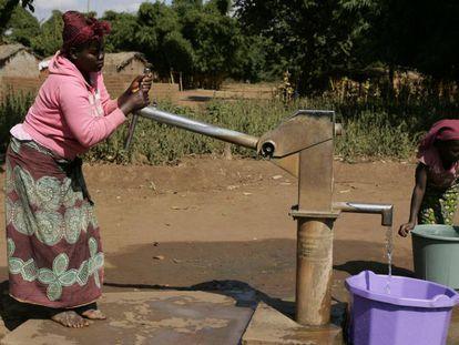 Una mujer, junto a su hija, saca agua de un pozo en su aldea en Malaui.