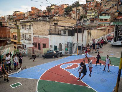 Niños y jóvenes juegan al baloncesto en una cancha restaurada por los vecinos en un barrio de Caracas.