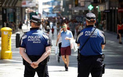 Dos policías municipales vigilan la calle de Preciados.