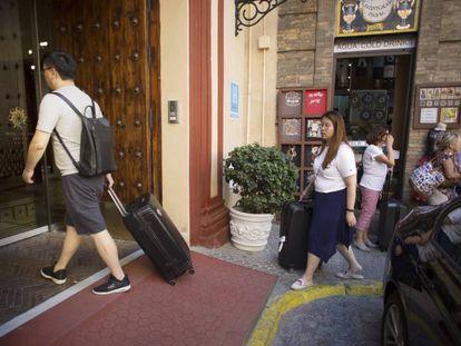 Varios turistas con sus maletas acceden a un hotel del centro de Sevilla.