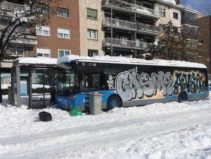 Un autobús de la EMT, atrapado en la nieve y con pintadas en una calle de Madrid.