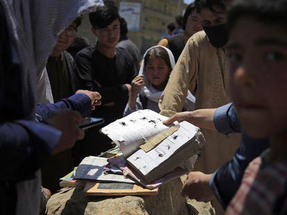 Un grupo de afganos recupera los libros de una escuela situada cerca del lugar de un bombardeo en Kabul, el 9 de mayo de 2021.