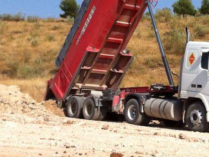 Uno de los camiones tirando tierra en la zona protegida.