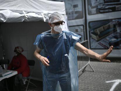 Un sanitario atiende a los ciudadanos en un puesto de campaña de test de covid-19 en Francia.