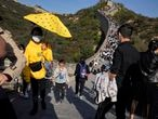 A child lowers his mask to enjoy an ice cream as he climbs up a stretch of the Badaling Great Wall of China on the outskirts of Beijing on Tuesday, Oct. 6, 2020. Chinese tourists took 425 million domestic trips in the first half of the eight-day National Day holiday, generating $45.9 billion in tourism revenue, according to China's ministry of culture and tourism. The holiday this year, which coincides with the Mid-Autumn Festival, will be a litmus test of whether China's tourism industry can bounce back after being battered by COVID-19. (AP Photo/Ng Han Guan)