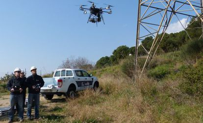 Unos operarios de Endesa supervisan los trabajos de comprobación de un dron.