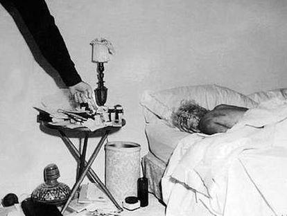 Fotografía inédita del cadáver de Marilyn Monroe en el dormitorio de su casa. Un policía, probablemente el sargento Jack Clemmons, señala las pastillas que provocaron la muerte de la actriz.