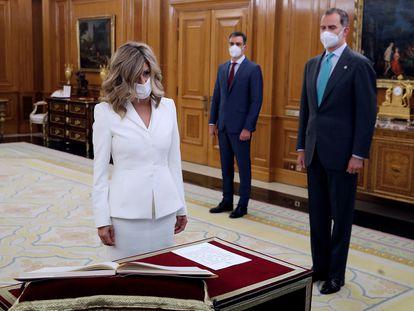 La ministra de Trabajo y nueva vicepresidenta tercera, Yolanda Díaz (izquierda), promete su nuevo cargo ante el rey Felipe VI (derecha) y el presidente del Gobierno, Pedro Sánchez.