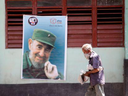 Un hombre camina ante una imagen de Fidel Castro, el lunes en La Habana (Cuba).