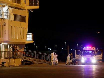 Personal médico traslada hacia una ambulancia a un pasajero del Greg Mortimer, el viernes 10 de abril.