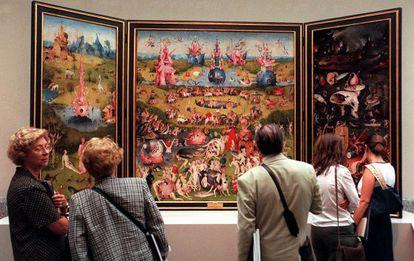 Varios visitantes contemplan 'El jardín de las delicias' de El Bosco en el Museo del Prado.