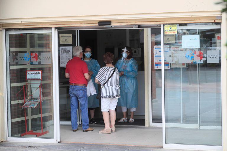 Dos personas se informan en la entrada del centro de salud V Centenariode San Sebastián de los Reyes.