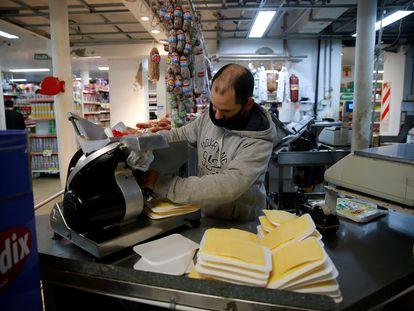 El trabajador de un supermercado empaca quesos en la ciudad de Buenos Aires (Argentina).