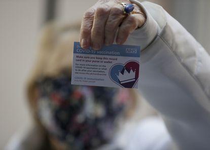 La británica Lyn Wheeler muestra su tarjeta de vacunación tras serle administrada la vacuna de Pfizer-BioNTech COVID-19 en un hospital de Londres.