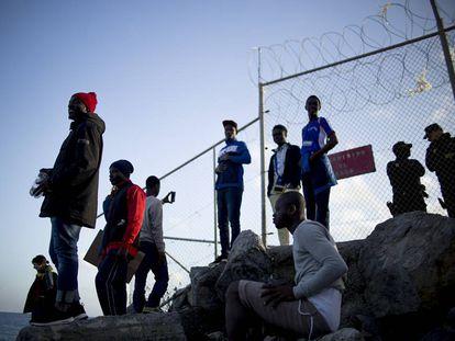 Varios jóvenes tras la valla que separa Ceuta de Marruecos donde cayó herido el chico de 16 años.