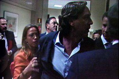 Imagen de televisión en la que el diputado del PP Rafael Hernando es sujetado por la socialista Carme Chacón en su incidente con Alfredo Pérez Rubalcaba.