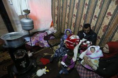 Un refugiado sirio sostiene, con la ayuda de su madre y su hermana, a sus trillizos recién nacidos en un parto en el que murió su esposa.