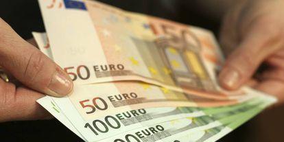 Una persona sostiene billetes de 50 y 100 euros.