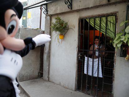 En agosto de 2020, durante el inicio del desconfinamiento en Argentina, un voluntario disfrazado como Mickey Mouse saluda a una niña encerrada en casa en Fuerte Apache, Buenos Aires. Fue una campaña por el Día del Niño en el país para animar a los más pequeños.
