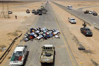 Combatientes rebeldes rezan en un puesto de control cerca de Abu Grein, unos 160 kilómetros al oeste de Sirte.