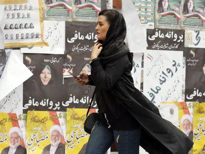 Una mujer pasa frente a unos carteles electorales, este miércoles en Teherán. En vídeo, declaraciones del líder supremo de Irán, Ali Jamenei.