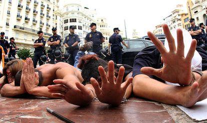Un grupo de indignados protesta ante  la policía en la plaza del Ayuntamiento de Valencia.
