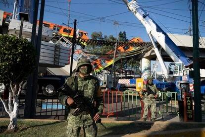 Dos militares vigilan la zona del accidente de la línea 12 del metro.