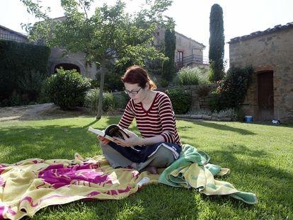 """Una mujer lee en el jardín de la casa """"Cal Prat Barrina"""", en la Sierra de Castelltallat, en la provincia de Barcelona."""