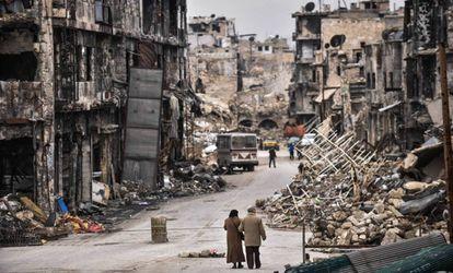 Una pareja recorre una de las calles de Alepo, con edificios reducidos a escombros.