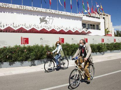 Asistentes al festival pasean en bicicleta frente al palacio del festival, este martes en Venecia.