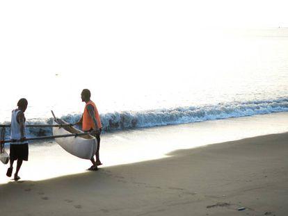 Dos pescadores de Vanuatu lanzan al agua su embarcación.