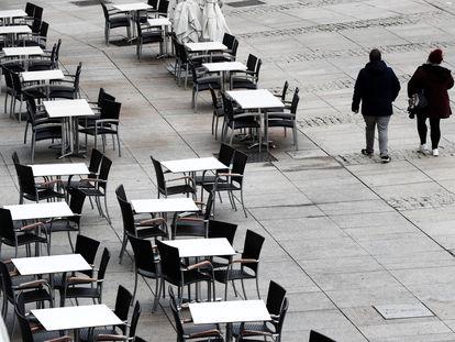 Dos personas caminan por la Plaza del Castillo, en Pamplona, al lado de mesas de las terrazas vacías, el 22 de octubre.